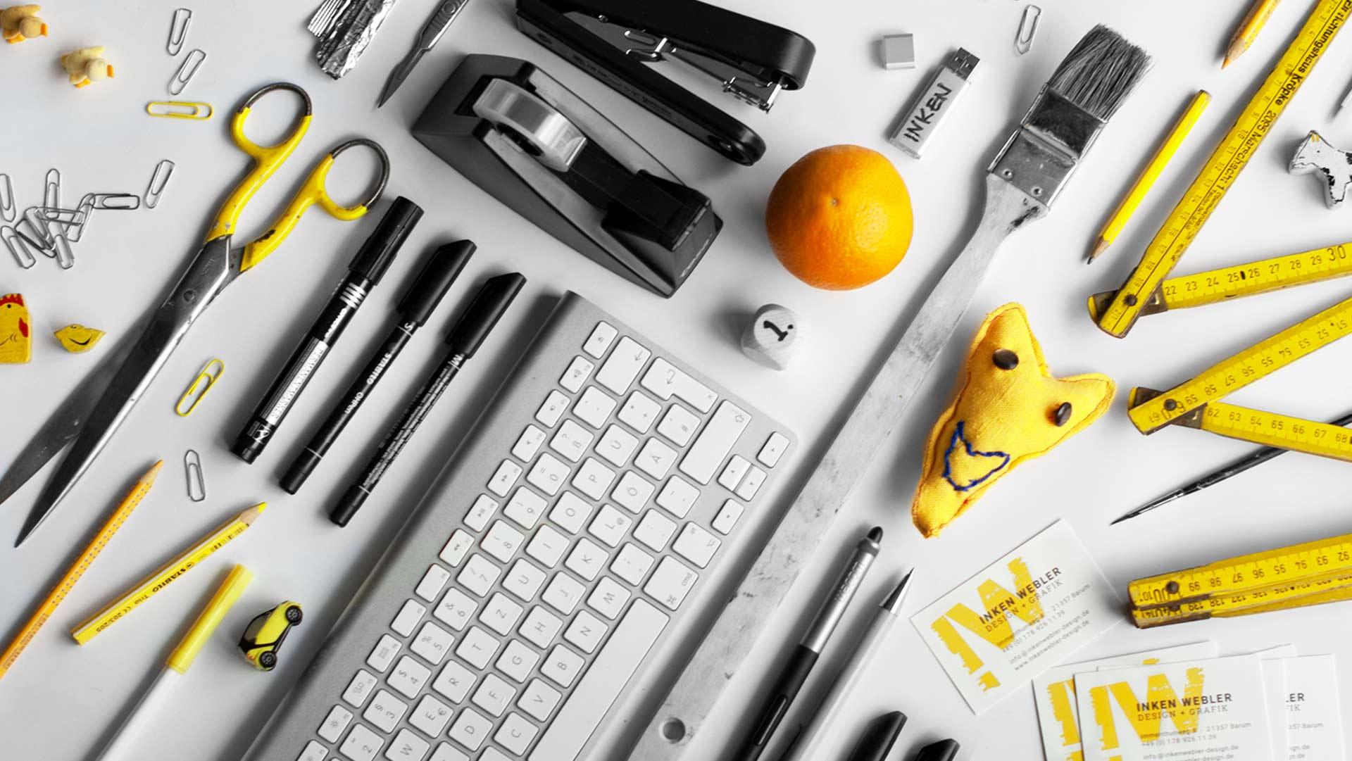diverse Arbeitsutensilien und Nützliches für Grafik und Webdesign - Tastatur, USB-Stick, Stifte, Pinsel, Schere, Tesafilm, Massstab, Herz, Nummer 1, Orange