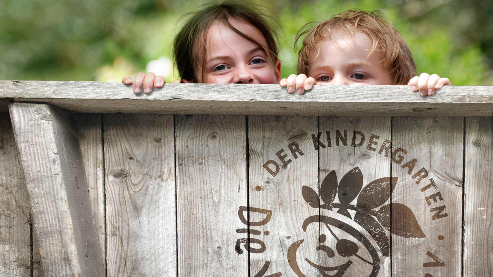 Zwei Kinder, die über eine Holzwand lugen, auf der Holzwand ein großes eingebranntes Logo