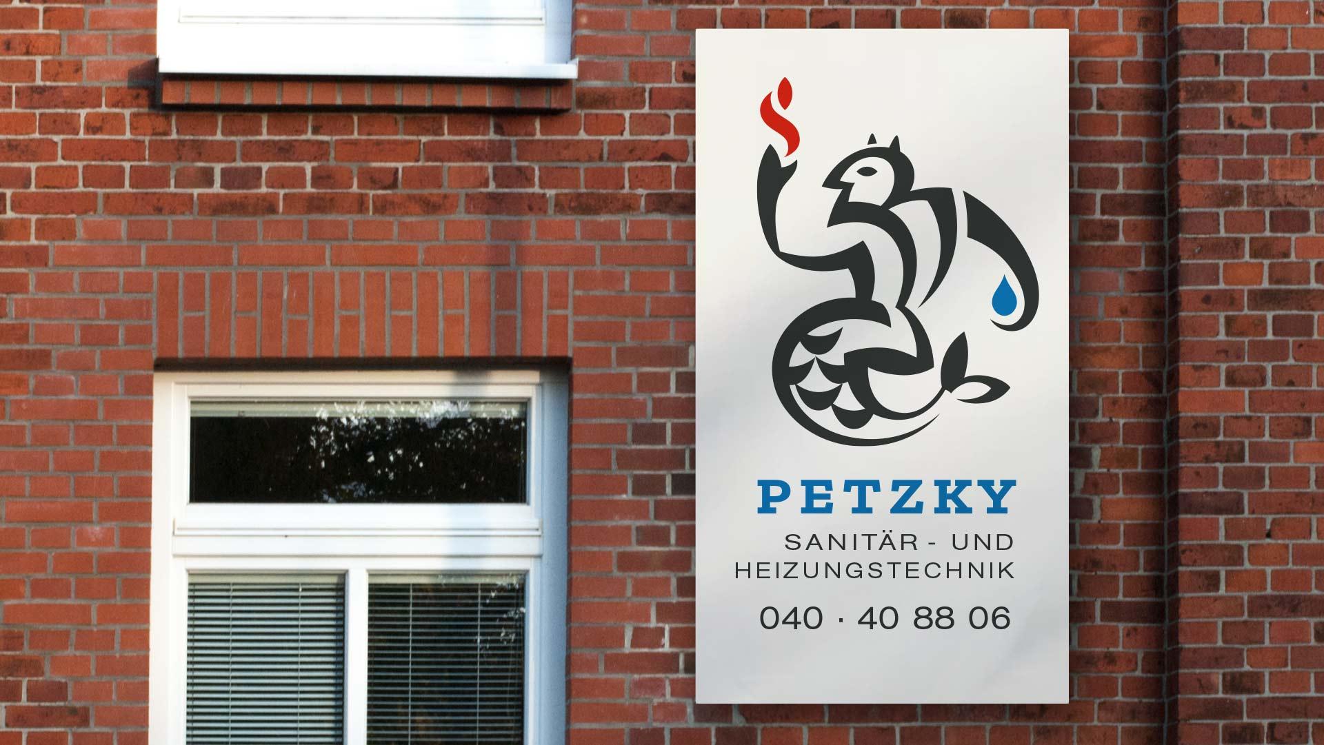 an einer Backsteinfassade hängendes Schild der Firma Petzky Sanitär- und Heizungstechnik