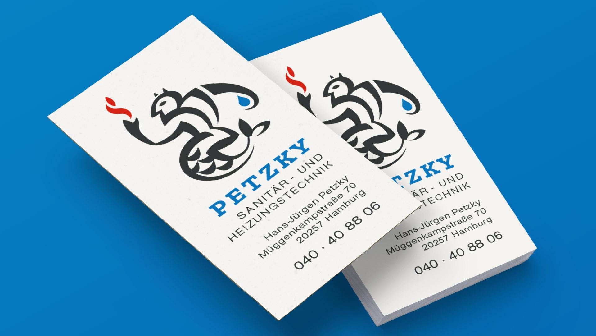 Visitenkarten Petzky Sanitär- und Heizungstechnik auf blauem Hintergrund