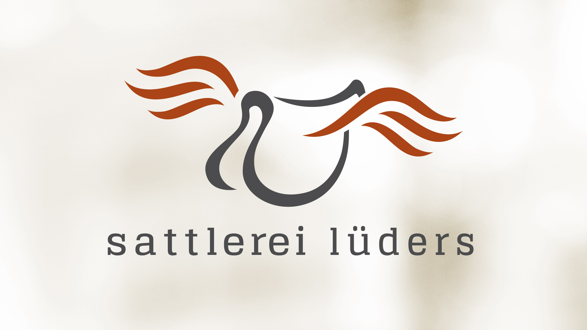 Logo Sattlerei Lüders - ein grauer Sattel mit rostfarbenen Flügelschwingen auf beigem Hintergund