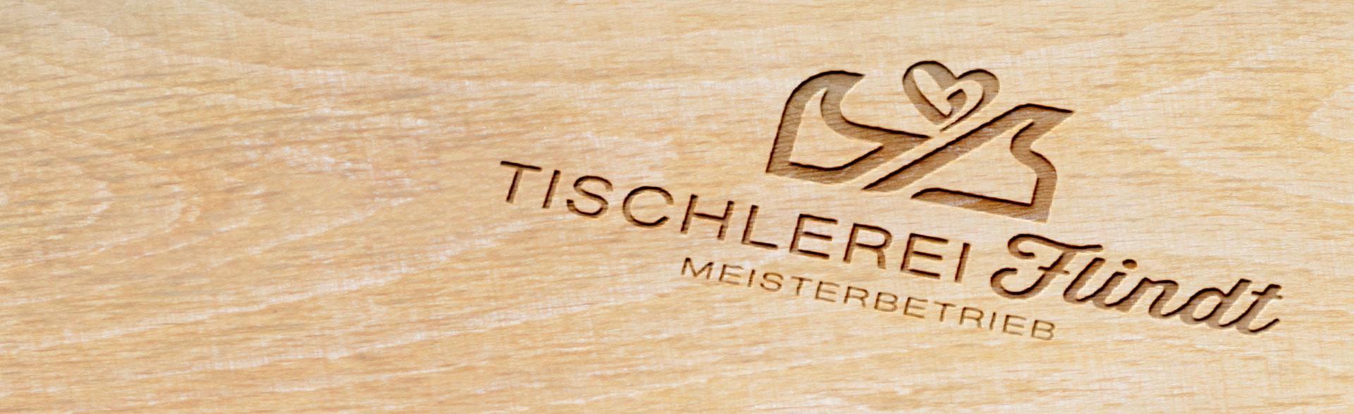 Logo Tischlerei Flindt Meisterbetrieb eingebrannt auf einem Stück Holz