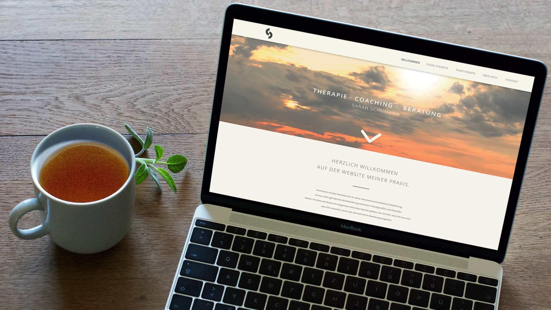 Ansicht eines Laptops auf einem Holztisch, daneben ein Becher Tee und ein frischer Salbeizweig - auf dem Laptop zu sehen ist die Starseiteder Website Sarah Schumanns