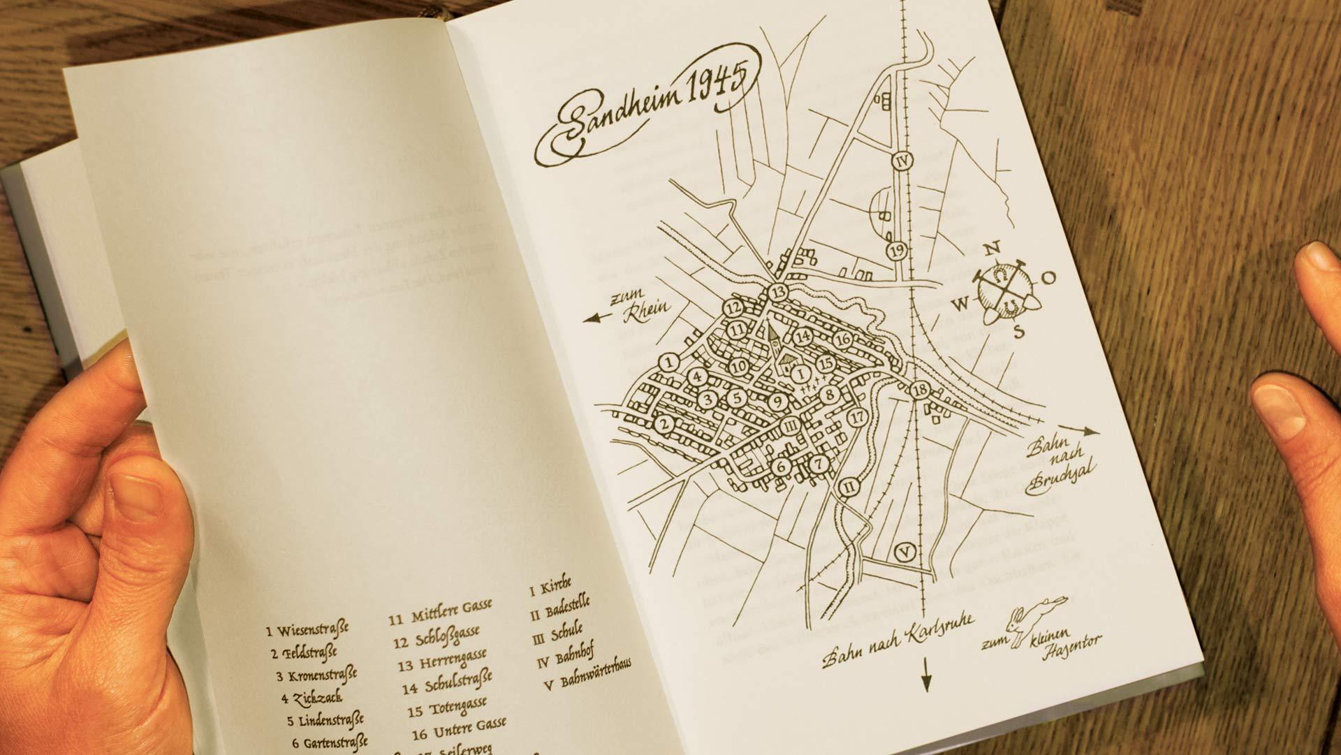 """Aufgeklappte Buchseite mit der beschrifteten Dorfkarten-Illustration des Buches """"Und doch ist es Heimat"""" von Jochen Metzger"""